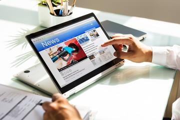 Businessman checking online news on laptop