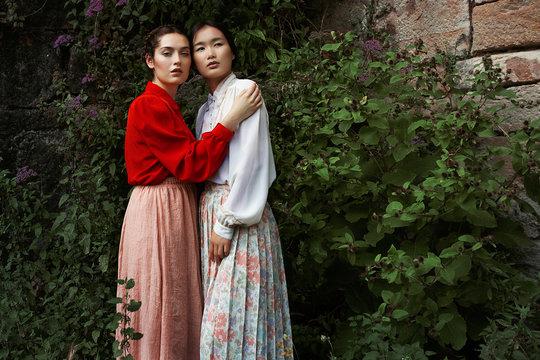 Attractive Multiethnic ladies embracing looking at camera