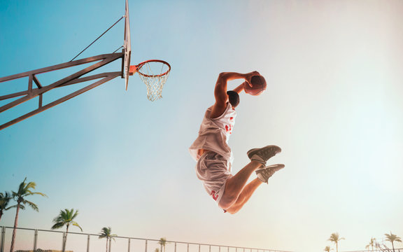 Streetball. Basketball player in action on sunset.