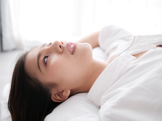 Happy Asian woman lying on bed, closed up.