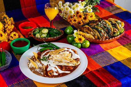 Enchiladas de mole con pollo y tacos de carnitas, comida mexicana en una mesa colorida