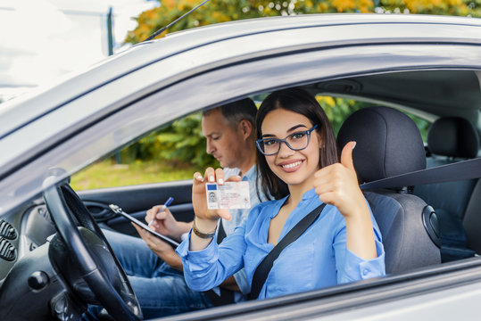 Driving school. Beautiful young woman successfully passed driving school test. She looking sitting in car, looking at camera and holding driving license in hand.