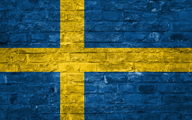 Flag of Sweden over an old brick wall background, surface