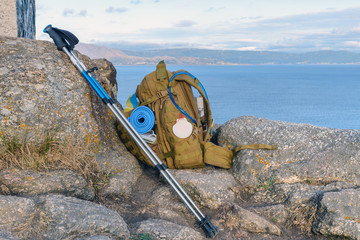 tourist backpack with walking sticks on the rock
