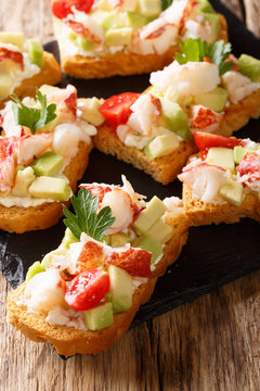 Italian bruschetta with lobster, avocado, tomatoes and cream cheese close-up. vertical
