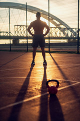 Fitness training outdoors. Handsome man working exercises in early morning with sunrise. Muscular...