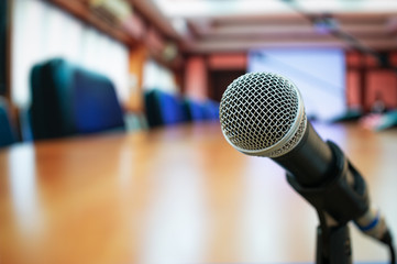 Microphones on abstract blurred of speech in seminar room or front speaking conference hall light, blure chairs for people in event meeting convention hall in hotel background
