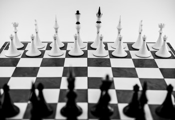 Black and white figures on a chessboard. Suitable for symbolic meaning in business, expression of strategy, desire for victory, defeat or gain