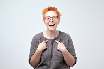 ff4a62a5dca Happy mature woman with red hair pointing fingers at herself. Select me  please concept