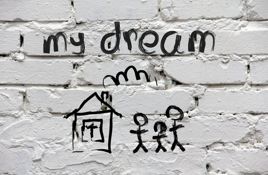 Brick wall with children's drawing of the house and family