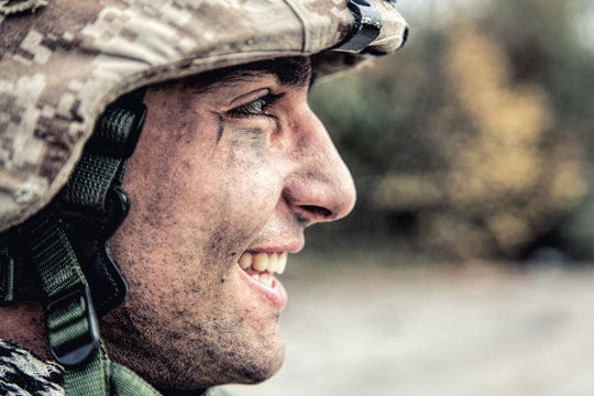 Shoulder portrait of happy smiling young soldier in battle helmet with scratches on camouflage, equipped U.S. army contractor, Marine Corps infantryman with dirty face looking at camera with friendly