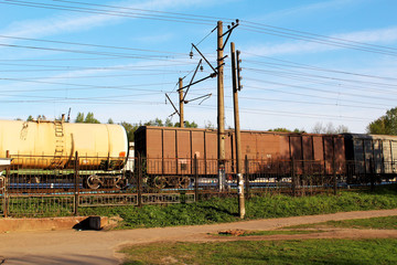 Wagons of a freight train behind a fence against a background of blue sky and electric wires