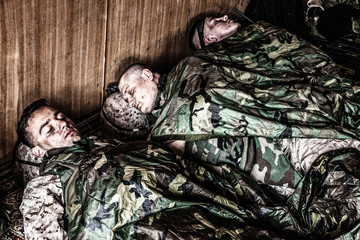 Tired U.S. marines resting at temporary base or camp, lying on floor in uniform and tactical ammunition, covered with poncho liners and sleeping bags, sleeping well after hard raid, exhausting mission