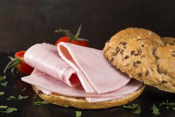 Open sandwich with sliced ham on a dark slate
