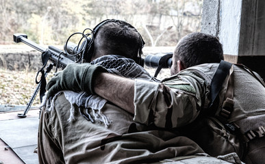 Military snipers team spotter observing battlefield, searching targets with binoculars, holding arm on shooters shoulder, correcting snipers fire with anti-materiel sniper rifle from hidden position