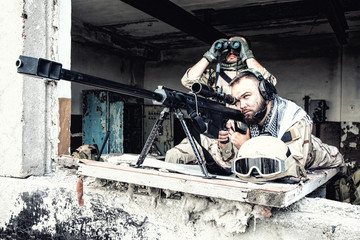 Navy SEAL sniper team, armed 50 caliber sniper rifle, observing territory, waiting in ambush, enemy forces surveillance, searching and engaging targets on range from position in city ruined building