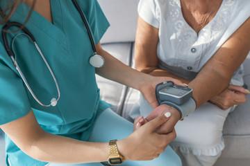 Delighted nurse measuring blood pressure