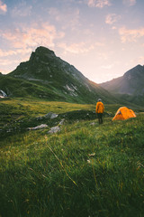 Camping in mountains man alone enjoying sunset landscape Travel adventure lifestyle concept active summer vacations with tent in wilderness