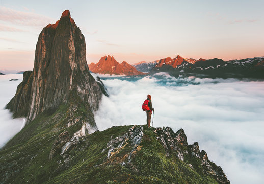 Traveler on cliff over clouds exploring sunset Segla mountain alone hiking adventure journey outdoor Norway vacations traveling lifestyle weekend getaway