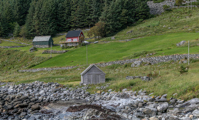 Rural Norwegian landscape with a house and two barns.