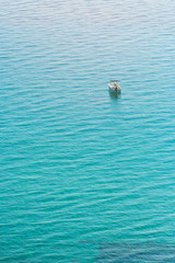 A lonely boat drifting in the sea. Empty white boat anchored on the water.