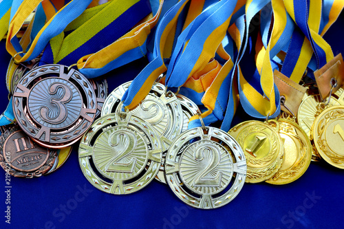Many gold, silver and bronze medals with yellow-blue ribbons