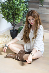 A beautiful girl with red curly hair sits on the wooden floor in denim shorts and a white shirt.