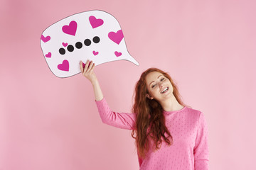 Portrait of cheerful woman holding thought bubble at studio shot