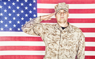 Portrait of U.S. army soldier in camouflage uniform and cap saluting on background of flag of United States of America, looking at camera. Military hand salute to display respect for national flag