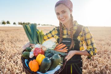 Frau trägt Korb mit lokal produziertem Bio Gemüse