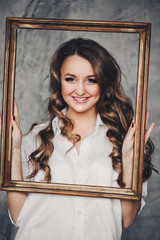 Studio portrait of happy beautiful girl in white shirt with wavy hair smiling at camera and holding photo or picture frame. She has make up and hairstyling after beauty salon.