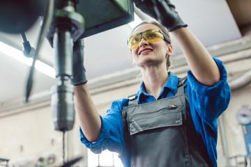 Arbeiterin in Schlosserei arbeitet an der Bohrmaschine