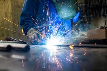 Schweißer in seiner Werkstatt beim Schweißen von Metall
