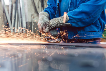 Metallarbeiter in Fabrik schleift Werkstück und Funken fliegen