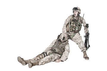 Commando soldier screaming and dragging backwards for plate carrier wounded and unconscious comrade. Tactical combat casualty care, injured combatant evacuating from battlefield, isolated on white