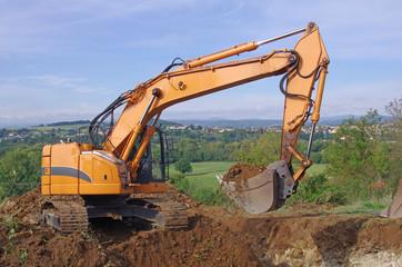 Pelleteuse à godet et à chenille en action, travaux de terrassement en vue de la construction d'un lotissement. Pelle mécanique hydraulique