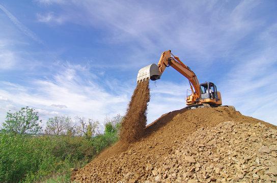 Pelleteuse à godet et à chenille en action, terrassement en vue de la construction d'une route. Entreprise de BTP. Pelle mécanique hydraulique