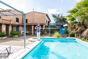 Mann steht am Rand seines Pools mit einem Pool Cacher und holt das Laub raus