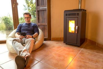 Mann sitzt am Kaminfeuer und liest entspannt ein eBook