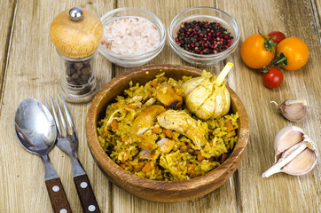 Rice with chicken meat and garlic in wooden bowl