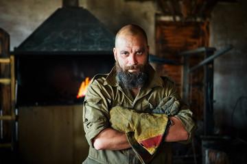 Portrait of a brutal, confident blacksmith, a man with a beard.