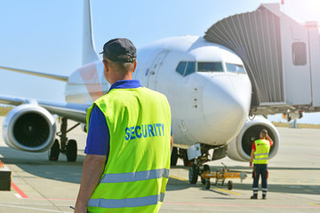 Airport security at work. Security guard monitors the situation near the aircraft boarding. .