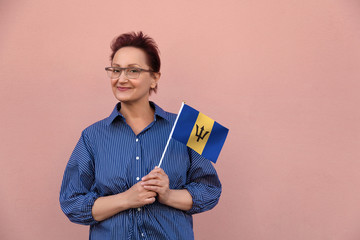 Barbados flag. Woman holding  Barbados flag. Nice portrait of middle aged lady 40 50 years old with a national flag over pink wall background outdoors.