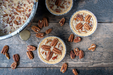 unbaked mini pecan pies on rustic table