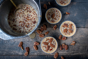 unbaked mini pecan pies on rustic table