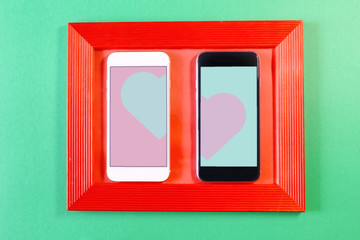 white and black smartphone in a red frame with a heart on a colored background