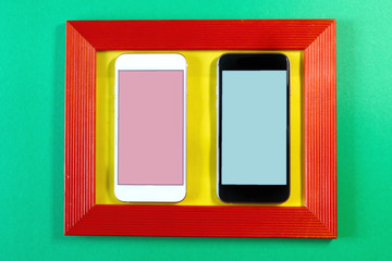 white and black smartphone in a red frame on a colored background