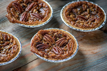 baked mini pecan pies on rustic table