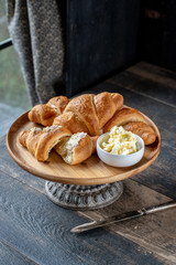 Golden croissants with butter on cake stand