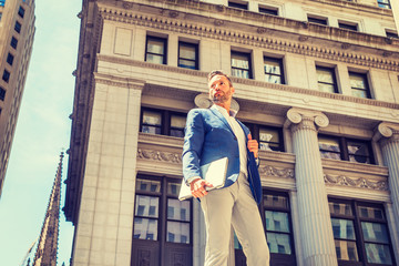 Young European Businessman with beard traveling, working in New York City, wearing blue blazer, gray pants, holding laptop computer, standing on street outside old office building, looking forward..